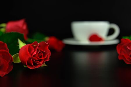 Red rose with cup of coffee in the evening. Black background