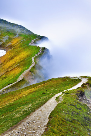 Beautiful view of path in foggy Tatra mountain. Starorobocianski peak Poland