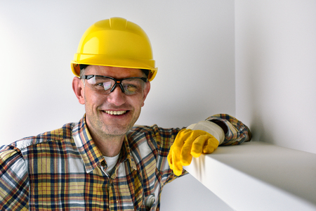 Construction worker wearing yellow helmet and smiling