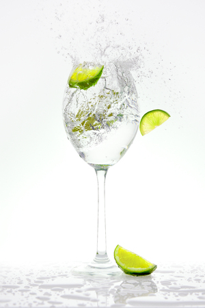 Fresh lime falling into a splashing sparkling water. 版權商用圖片