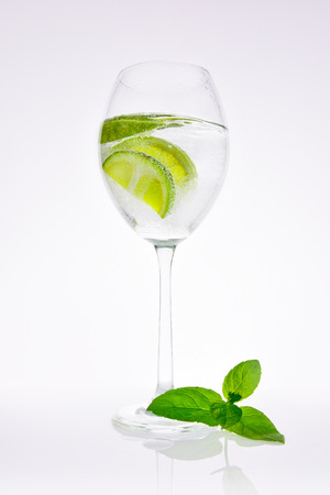 Lime in carbonated water with a mint leaf. White background 版權商用圖片