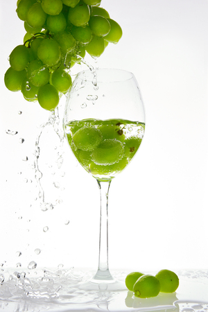 Green grape with water splash into glass. White background 版權商用圖片
