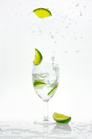 Slice of lime pops from a glass with sparkling water