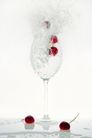 Red flying cherries pop out of a glass with sparkling water