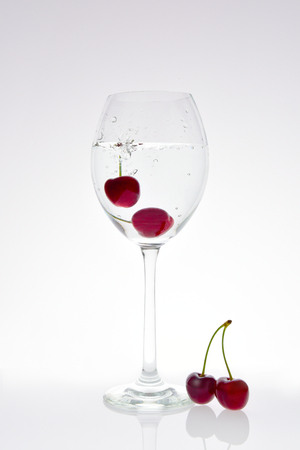 Cherries fall into a glass with sparkling water