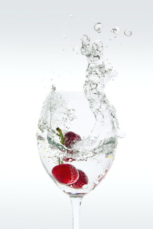Splash of carbonated water in a glass with cherries