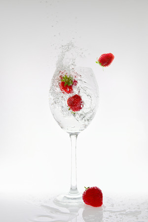 Splash of carbonated water in a glass with strawberries