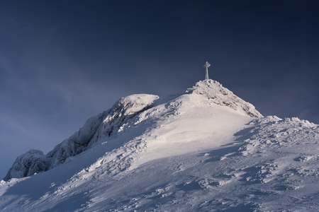 Snow covered cross on the mountain top Giewont. Polish national park