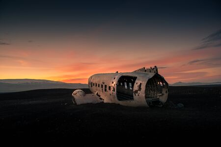 Airplane wreck on a black beach at the sunset. Iceland