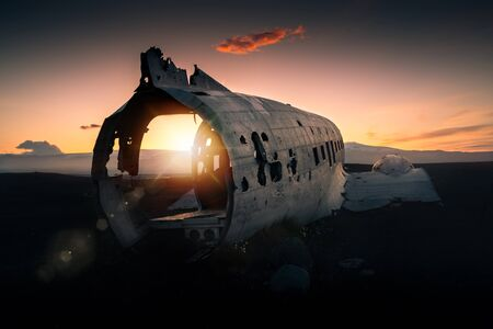 Crashed plane Dakota on black beach at the sunset