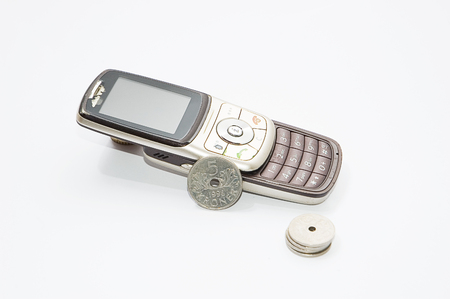 old cell phone: Old cell phone ruined and scratchy and Norwegian currency