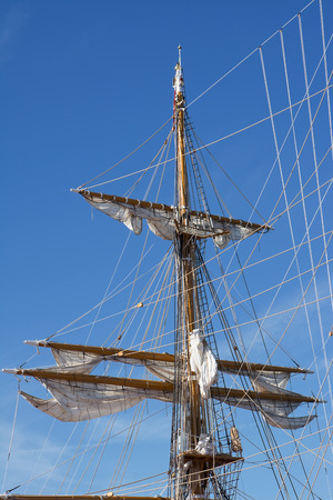 furled: Mast of sail ship in blue sky Stock Photo