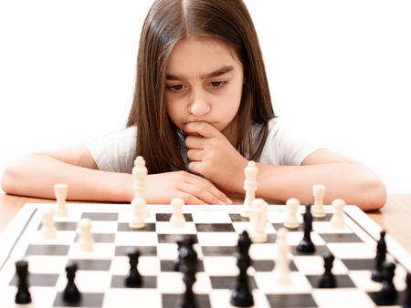 beautiful little girl concentrated playing chess Stock Photo