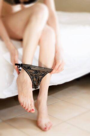 fille nue sexy: Sur le lit, prenant sa culotte Banque d'images