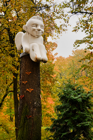 garden statuary: Angel statue sitting on the pole in the park of Vilnius Stock Photo