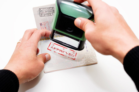 visa approved: Stamping passport with red stamp approved Stock Photo