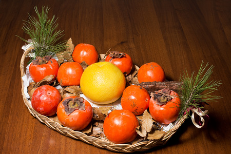 khakis: Composition of persimmon, grapefruit and pine cone in the dish on table