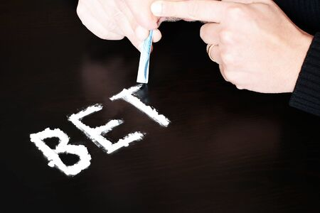 bets: Concept of addiction for bets and gambling with man sniffing a cocaine Stock Photo