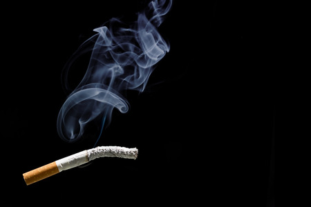 carcinogen: Cigarette burning and smoke with  black background Stock Photo