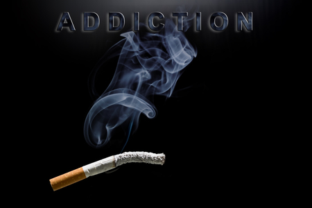 carcinogen: Burning cigarette, smoke and text addiction Stock Photo