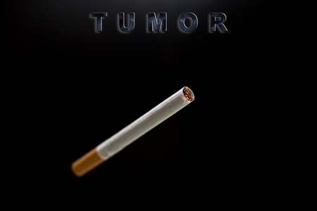 carcinogen: cigarette, text tumor on black background Stock Photo