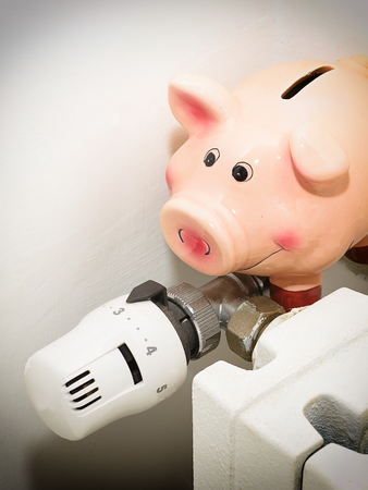 save heating costs: Piggy bank and the valve on the radiator for energy savings