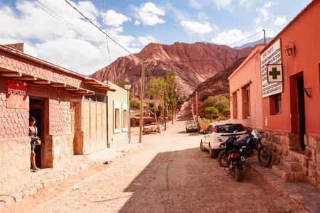 Purmamarca, Argentina - November 1, 2016: Street in Purmamarca with indigen woman and car (Argentina)