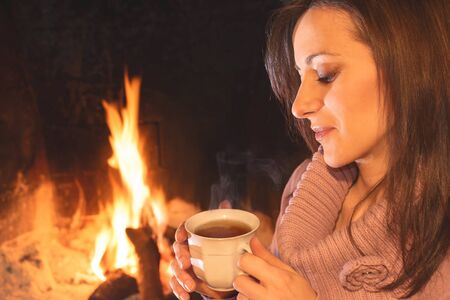 Pretty woman reading ebook sitting near the hearth stock photo pretty woman drinking a cup of hot drink near the hearth photo fandeluxe Ebook collections
