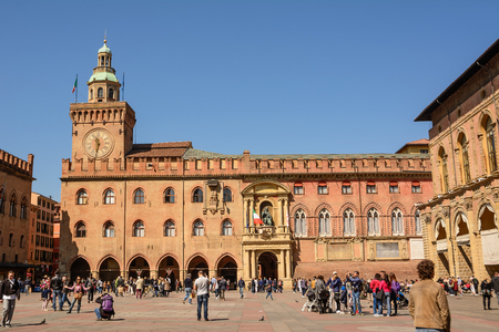 Bologna, Italy - April 22, 2017: Palace of Accursio in Piazza Maggiore of Bologna with tourists on a sunny day Editorial
