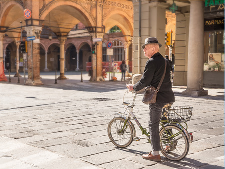 Bologna, Italy - April 22, 2017: Senior bicycle man in the center of bologna in a sunny day