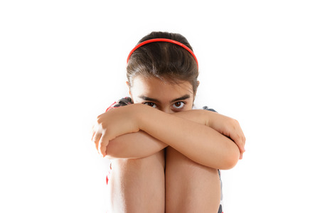 A Baby girl with her head hiding in her arms Stock Photo