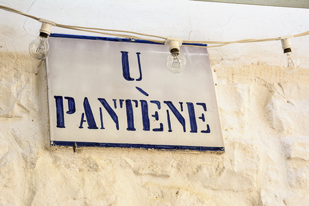 Road sign with street dialect name in a Puglia road