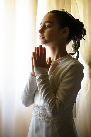 Klein meisje bidden tot de eerste communie Stockfoto