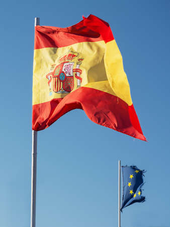flagstaff: Spanish flag and in the background the flag of the European community consumed