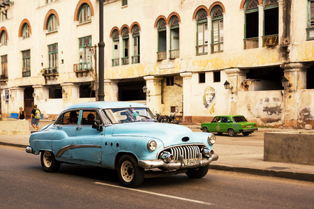 Havana, Cuba - December 3, 2017: blue, old and classical car in road of old Havana (Cuba) and in the background the icon of Che
