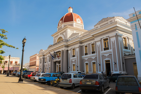 Cienfuegos, Cuba - December 7, 2017: Cienfuegos Municipal Palace and parked cars