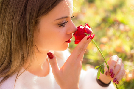 A Girl sniffing a red rose in San Valentine day Stock Photo