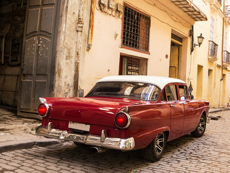 Back Red old and classical car in road of old Havana (Cuba)
