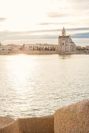 Cathedral built near the sea in Puglia at sunset Redactioneel