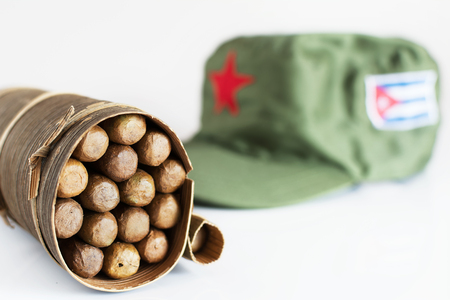 Some Cuban cigars rolled in banana leaf and military cap on the background