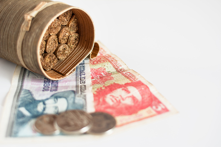 Some Cuban cigars and blurred cuban pesos with heroes icon of Guevara and Cienfuegos Stock Photo
