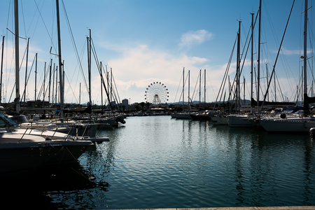 Boats moored in the marina of Pescara at sunset and the Ferris wheel background