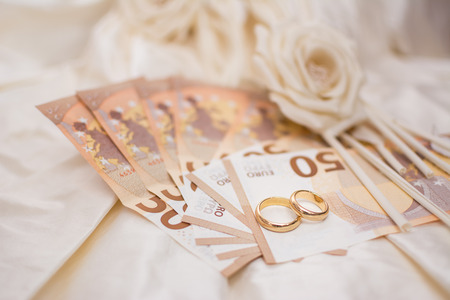 Wedding rings and banknotes with a wedding dress on the background Stock Photo