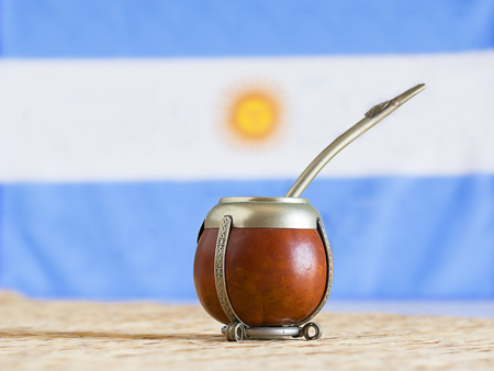mate, mate grass (yerba mate) with flag of Argentina  in the background Foto de archivo