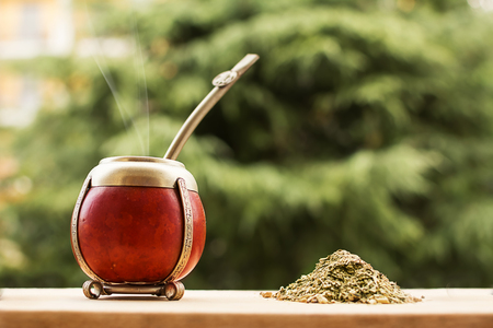 mate, mate grass (yerba mate) and steam with trees in the background
