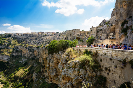 Matera, Italy - August 18, 2018: Panorama of the gravina with the ancient area of Matera and tourists on the road 에디토리얼