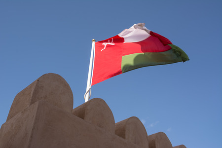 Scalloped walls of the Nahkal Fort and its flag in the wind (Oman) Editorial
