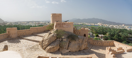 Walls and turrets of the Fort of Nahkal and the village with the mosque in the background (Oman)