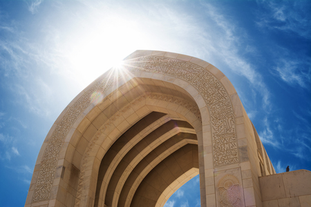 Detail of an arch of the Muscat Grand Mosque with sun in backlighting (Oman)