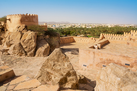 Walls of the Fort of Nakhal and the village with the mosque in the background (Oman) Editorial